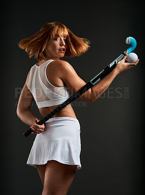 Buy stock photo Cropped shot of a beautiful young woman posing with hockey equipment against a grey background