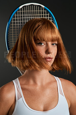 Buy stock photo Shot of a young woman posing with a tennis racket against a dark background