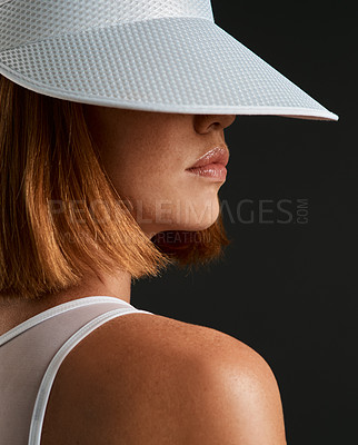 Buy stock photo Cropped shot of a sporty young woman wearing a sun visor against a dark background