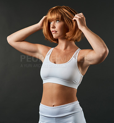Buy stock photo Cropped shot of a sporty young woman posing against a dark background