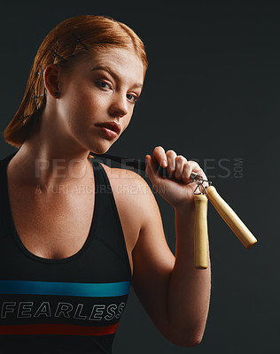 Buy stock photo Studio portrait of a sporty young woman posing with a skipping rope against a black background