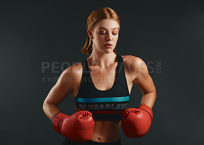 Buy stock photo Studio shot of a sporty young woman wearing boxing gloves against a black background