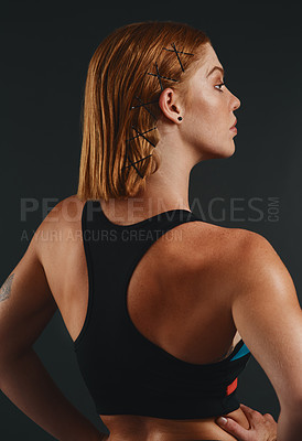 Buy stock photo Studio shot of a sporty young woman posing against a black background