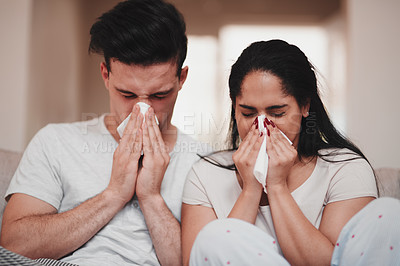 Buy stock photo Cropped shot of a young couple blowing their noses while sitting on the living room sofa