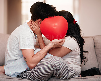 Buy stock photo Cropped shot of an unrecognizable young couple kissing behind a heart-shaped balloon on valentine's day