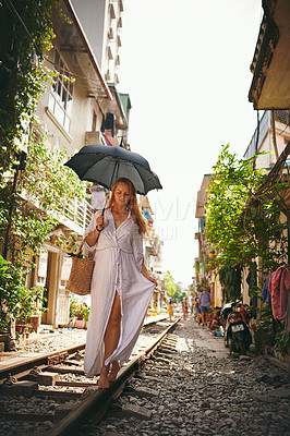 Buy stock photo Shot of a woman walking on the train tracks while exploring a foreign city