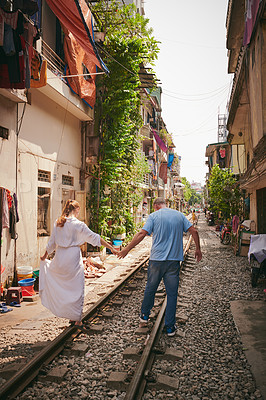 Buy stock photo Shot of an affectionate couple on a railway track while exploring a foreign city