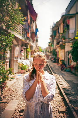 Buy stock photo Shot of a woman walking on train tracks while exploring a foreign city