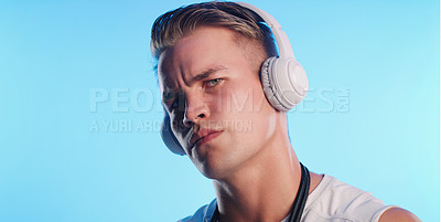 Buy stock photo Studio portrait of a young man posing with a skipping rope and headphones against a blue background