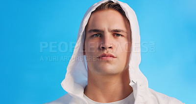 Buy stock photo Studio portrait of a handsome young man posing in a hooded sweater against a blue background