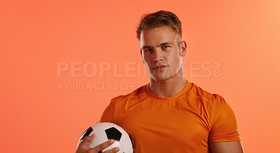 Buy stock photo Studio portrait of a handsome young male soccer ball player posing with a ball against an orange background
