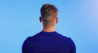 Buy stock photo Rearview shot of an unrecognizable young man posing against a blue background