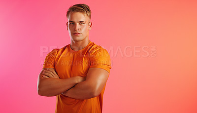 Buy stock photo Studio portrait of a handsome young man posing with his arms crossed against a peach background