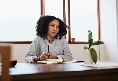 Buy stock photo Shot of a young woman looking thoughtful while working at home