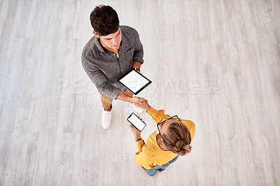 Buy stock photo High angle shot of two young designers shaking hands while using digital devices in an office