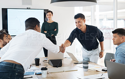 Buy stock photo Shot of businessmen shaking hands during a meeting in a modern office