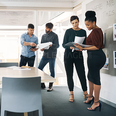 Buy stock photo Shot of a group of businesspeople discussing paperwork during a meeting in a modern office