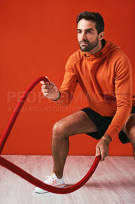 Buy stock photo Studio shot of a handsome young man working out with battle ropes against a red background