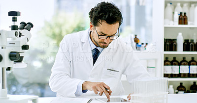Buy stock photo Shot of a young scientist using a digital tablet while going through paperwork in a lab