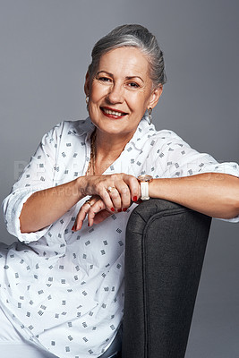 Buy stock photo Studio shot of a senior woman sitting on a chair against a grey background