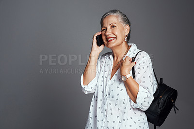 Buy stock photo Cropped shot of a senior woman carrying her handbag while talking on her cellphone