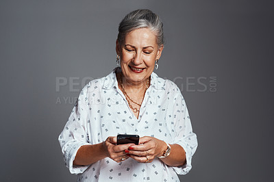 Buy stock photo Studio shot of a senior woman using her cellphone while standing against a grey background
