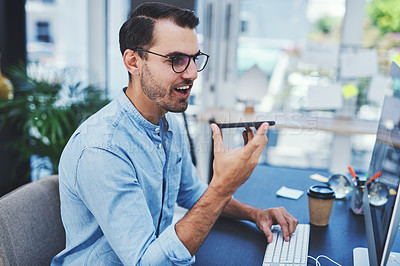 Buy stock photo Shot of a young designer using a cellphone while working on a computer in an office