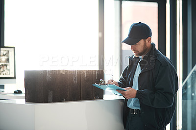 Buy stock photo Shot of a handsome delivery man writing on his clipboard while waiting in the lobby with a customer's order