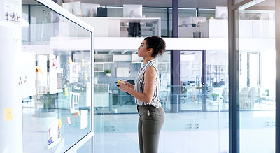 Buy stock photo Shot of a young businesswoman brainstorming ideas and writing notes on a glass wall inside her office