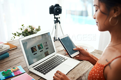 Buy stock photo Cropped shot of an attractive young businesswoman sitting and using her cellphone while blogging from her laptop