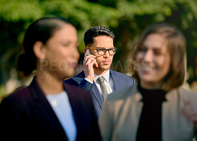 Buy stock photo Defocused shot of a man talking on his cellphone while standing outdoors