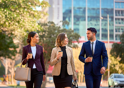 Buy stock photo Shot of three businesspeople having a discussion while walking through the city