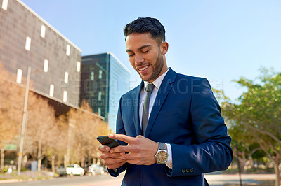 Buy stock photo Shot of a young businessman using his cellphone while out in the city