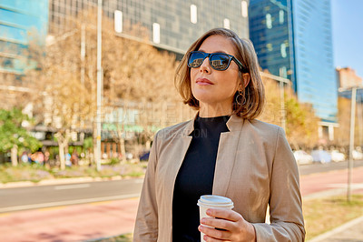 Buy stock photo Shot of a businesswoman holding a coffee while out in the city