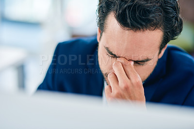 Buy stock photo Shot of a young businessman suffering with a headache while working in an office