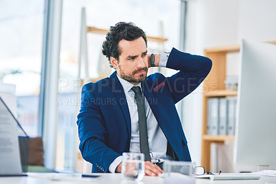 Buy stock photo Shot of a young businessman suffering with neck pain while working on a computer in an office