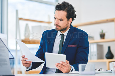 Buy stock photo Shot of a young businessman using a digital tablet while going through paperwork in an office