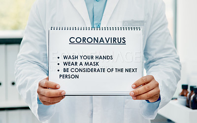 Buy stock photo Shot of a scientist holding a sign with a list of COVID-19 prevention measures on it in a laboratory