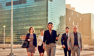 Buy stock photo Shot of a group of well-dressed businesspeople walking through the city during the day