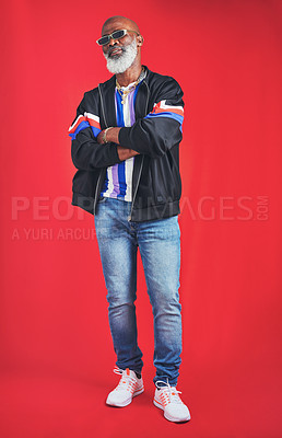 Buy stock photo Studio shot of a senior man wearing retro attire while posing against a red background