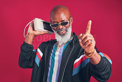 Buy stock photo Studio shot of a mature man holding a cassette player against a red background