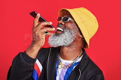 Buy stock photo Studio shot of a mature man holding his cellphone against a red background
