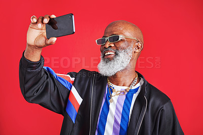Buy stock photo Studio shot of a senior man taking a selfie against a red background