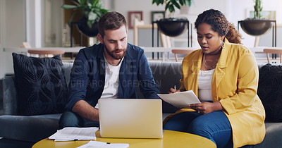 Buy stock photo Shot of two businesspeople using a laptop while going through paperwork together in an office