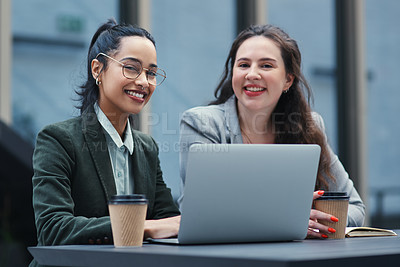 Buy stock photo Shot of two young businesswomen using a laptop during a meeting at a coffee shop