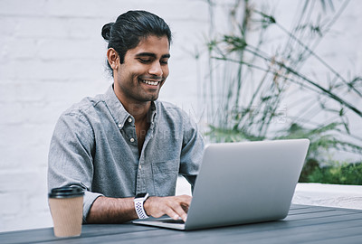 Buy stock photo Shot of a young businessman using a laptop and having coffee in a modern workplace
