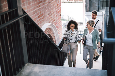 Buy stock photo Shot of two businesswomen having a discussion while walking up the stairs in a modern workplace