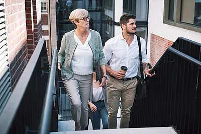 Buy stock photo Shot of a group of businesspeople walking up the stairs in a modern workplace
