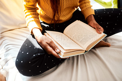 Buy stock photo Cropped shot of an unrecognizable man reading a book while sitting on her bed