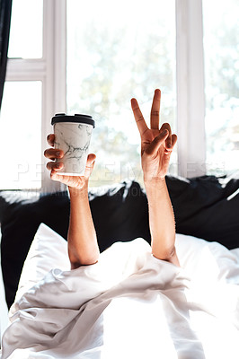 Buy stock photo Cropped shot of a woman lying in the covers whole holding up a coffee and showing the peace sign